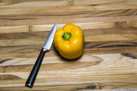 Yellow pepper on cutting board alongside a paring knife