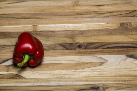 Red Bell pepper on a teak cutting board