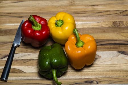 paring knife: Colorful peppers on cutting board with a paring knife