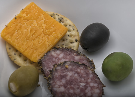 sesame cracker: selection of cheddar cheese,peppered hard salami, a sesame cracker and three colorful olives