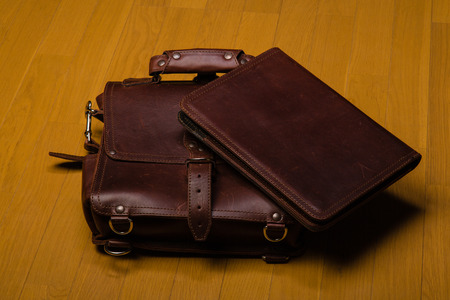 attache: Brown worn leather briefcase and portfoilia on a hardwood floor