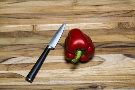 Pimiento rojo y un cuchillo de pelado en una tabla de cortar de madera de teca Foto de archivo - 41842386