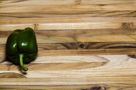 Green bell pepper on a teak cutting board