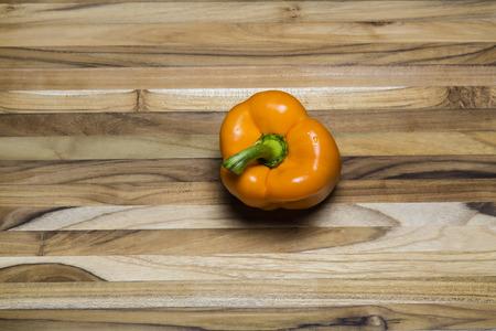 Orange bell pepper on a teak cutting board