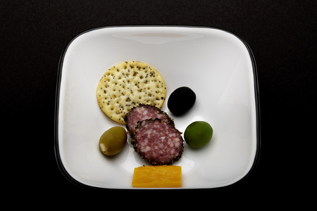 sesame cracker: selection of cheddar cheesepeppered hard salami a sesame cracker and three colorful olives
