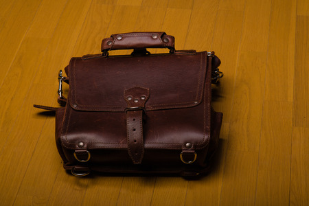 leather briefcase: Brown leather briefcase lying on a hardwood floor