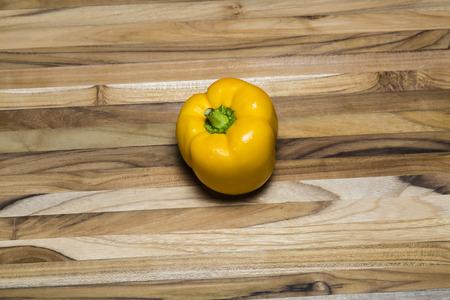 Pimienta amarilla en una tabla de cortar de madera de teca Foto de archivo - 41842473
