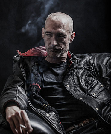 Stern looking middle aged man smoking against a dark background 스톡 콘텐츠