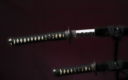 wakizashi: Samurai sword partially out of the sheath sit over the short sword on a dark background with a red spot light Stock Photo