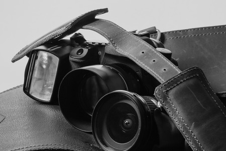 contrasted: Modern camera gear contrasted with and old fashioned leather gear bag in Black and white retro look