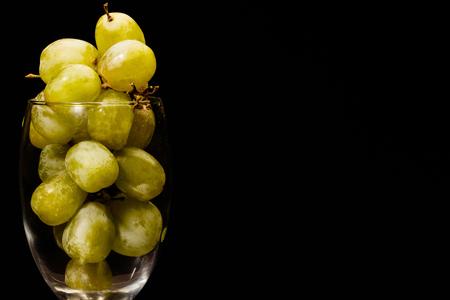 copa de vino: Uvas verdes en un vaso de vino contra un fondo oscuro