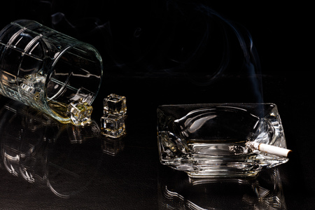 cut glass: A glass of spilled whiskey and ice cubes next to a burned to the filter cigarette in a cut glass ashtray against a dark background