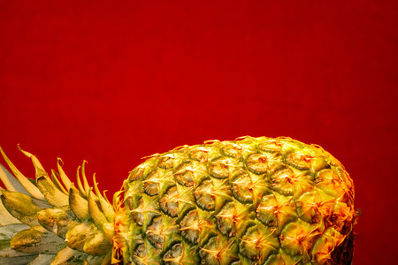 healthful: A ripe whole pinapple laying down against a colorful background