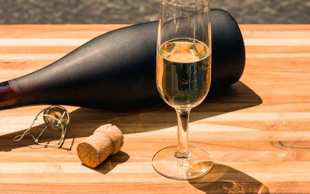 Fles champagne en fluit met kurk op een teak boord Stockfoto