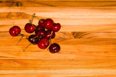 Cerezas maduras frescas en una tabla de cortar de madera de teca Foto de archivo - 58594633