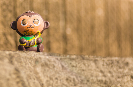 gouged: A worn and damaged toy monkey sitting on a stone wall. Stock Photo