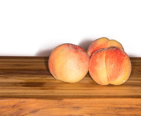 Tres melocotones maduros (Prunus persica) en una tabla de cortar de teca sobre un fondo blanco Foto de archivo - 68475791