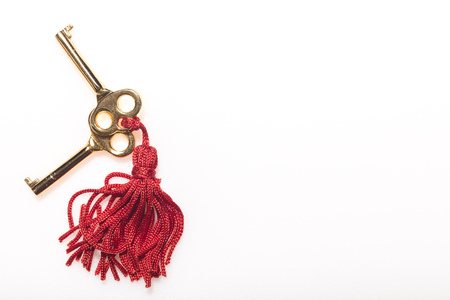 Two skeleton keys on a red tassel against a white background
