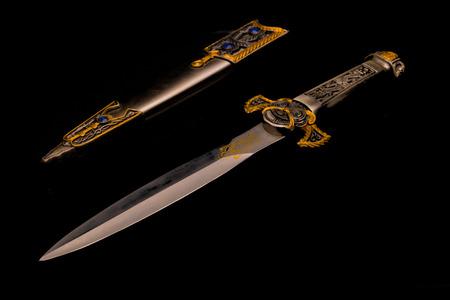 A ceremonial dagger alongside a jeweled sheath against a reflective black background Stok Fotoğraf