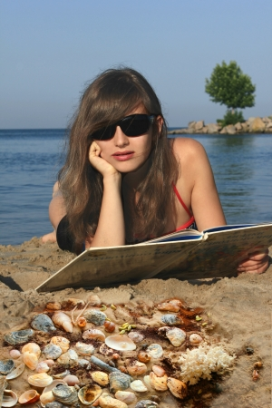 Girl with a book on the beach     photo