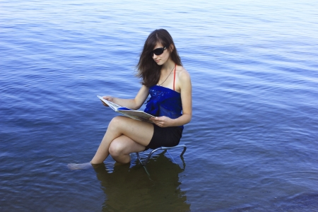 Girl with a book on the sea  photo