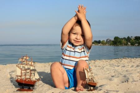 a little boy on the beach with a ship Stock Photo
