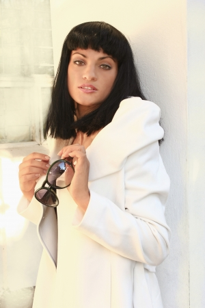 girl with black hair in a white coat    photo
