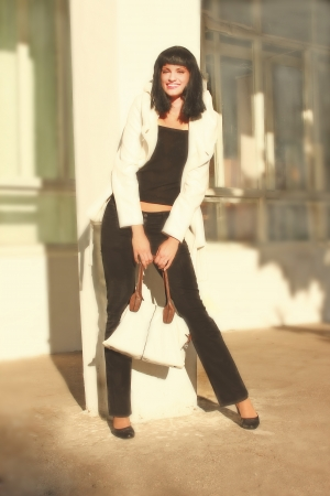 woman s bag: girl with black hair in a white coat with a woman s bag