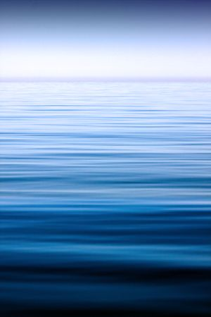 calm background: A scene with calm sea extending to the horizon, under the clear sky. Stock Photo
