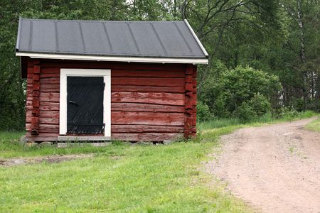 A very small red log hut in the countryside in Finland. Stock Photo - 5059971