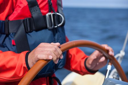 lifevest: A sailor wearing a life vest steering a sailboat on a beautiful summer day. Stock Photo