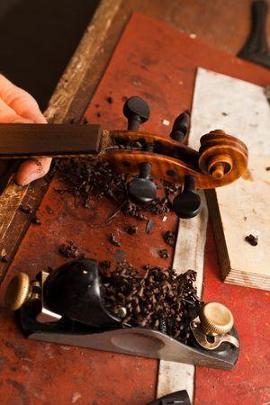 violin making: A violinmaker making repairs on a violin in his shop. Stock Photo