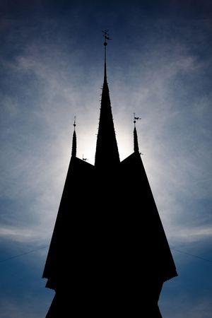 menacing: A menacing silhouette of a clocktower against the sun.
