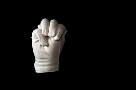 A white gloved hand isolated on black background. American sign language alphabet M. photo