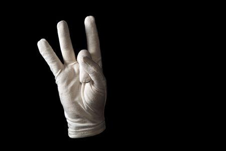 gloved: A white gloved hand isolated on black background. Sign language number eight.