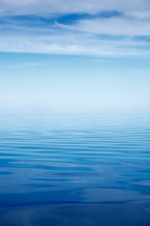 extending: A scene with calm sea extending to the horizon, under the clear sky. Stock Photo