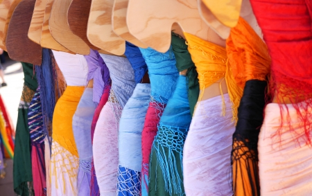 A line of brightly-colored bohemian and belly-dance dresses and outfits on mannequin hangers at a Renaissance Fair