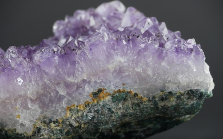 A close up of an amethyst crystal geode from the side, with a gray background  Stok Fotoğraf