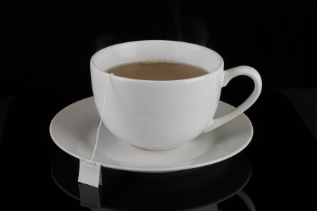 Angled view of a white cafe-style tea cup with tea and tea bag on a saucer against a black background
