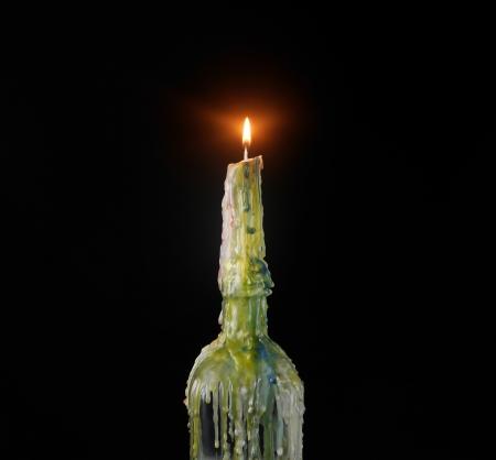 samhain: A spooky vela m�gica de aspecto que ha goteado cera de varios colores sobre una botella de vidrio con una llama brillante sobre un fondo negro Foto de archivo