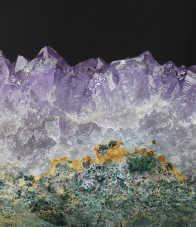A close up of an amethyst crystal geode from the side in profile, with a gray background  Recommend use  Composite and use as a crystal mountain range