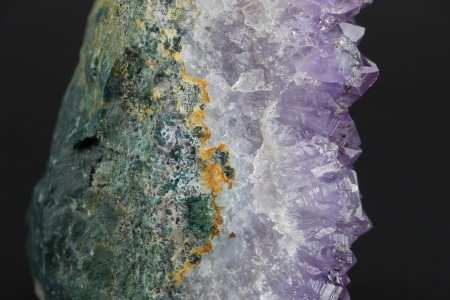 A close up of an amethyst crystal geode from the side in profile, with shallow depth of field and a gray background  Stock Photo