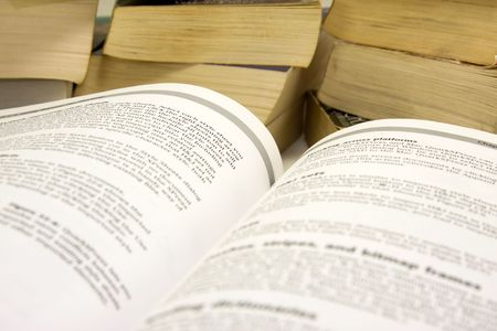 Open book with stack of paperback books in background. Stock Photo