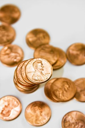 A stack of pennies surrounded by pennies against a white background.