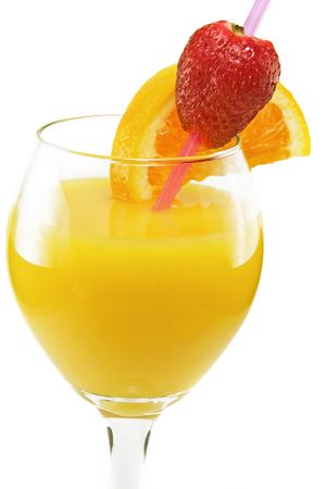 Fresh orange juice with a fresh strawberry and orange slice in a wine goblet against a white background.