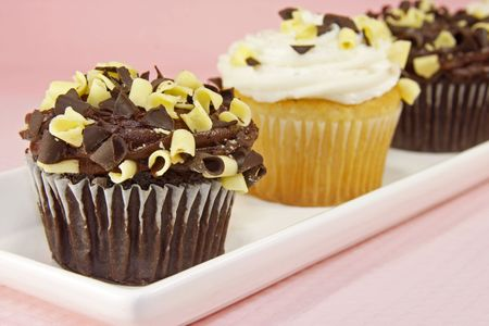 Chocolate and vanilla cupcakes on white plate against a pink background.