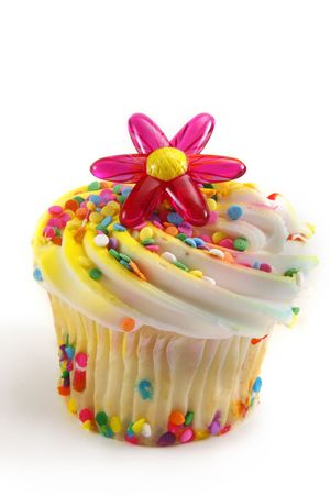Cupcake decorated with white icing, sprinkles and a plastic flower.