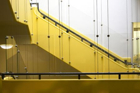 stairwell: Empty yellow stairwell with glass safety panels. Stock Photo