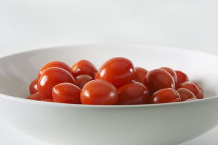 Cherry tomatoes in a white bowl against a white background.  photo