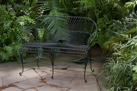 Bench in a garden setting surrounded by green palms and foliage.  Stock Photo